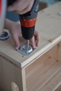 Vissage des accroche qui permettent de visser les pieds du meuble